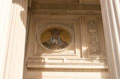 Vecchia costruzione della facciata con le colonne con l'icona Fotografia Stock