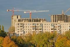 Vecchia costruzione di appartamento contro la gru di costruzione Immagine Stock Libera da Diritti