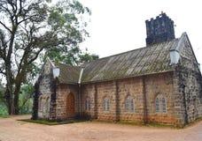 Vecchia costruzione di chiesa storica fatta delle pietre e di un albero enorme - Muunar, Kerala, India Immagini Stock Libere da Diritti