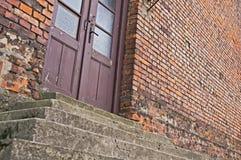 Vecchia costruzione di mattone con i punti di pietra e le porte di vetro di legno immagine stock