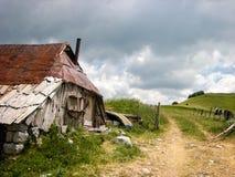 Vecchia e cabina rustica della montagna fatta di metallo, della pietra e del legno Immagini Stock Libere da Diritti