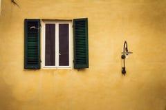 Vecchia e finestra rustica con gli otturatori verdi accanto ad una lampada fotografia stock libera da diritti