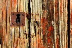 Vecchia e porta di legno stagionata e foro chiave arrugginito del ferro Immagini Stock Libere da Diritti