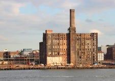 Vecchia fabbrica di abbandono al pilastro con il fiume in priorità alta Fotografia Stock Libera da Diritti
