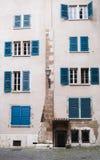 Vecchia facciata della casa con gli otturatori di legno blu fotografia stock libera da diritti