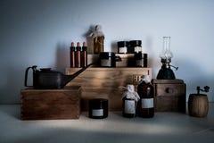 Vecchia farmacia bottiglie, barattoli, lampada di cherosene sugli scaffali di legno Immagine Stock