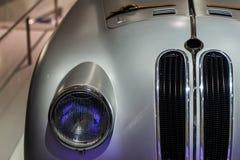 Vecchia fine metallica grigia dell'automobile su della griglia di radiatore e del faro fotografia stock