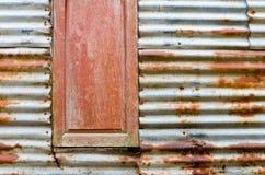 Vecchia finestra arrugginita sulla parete della lastra di zinco Immagine Stock Libera da Diritti