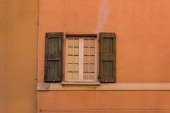 Vecchia finestra con gli otturatori di legno, ciechi del sole sul passo arancio luminoso fotografia stock