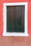 Vecchia finestra con gli otturatori verde scuro sulla parete rossa fotografia stock libera da diritti