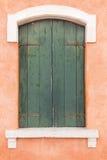 Vecchia finestra con gli otturatori verdi sulla parete arancione-chiaro fotografia stock libera da diritti