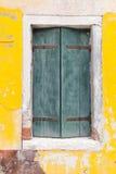 Vecchia finestra con gli otturatori verdi sulla parete gialla fotografie stock