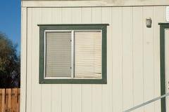 Vecchia finestra con i ciechi di finestra di plastica con le pareti di legno immagini stock libere da diritti
