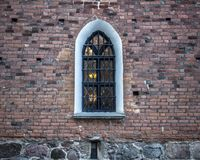 Vecchia finestra della chiesa in Scandinavia, inquadratura bianca e muro di mattoni immagini stock