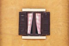 Vecchia finestra di Brown con la tenda sulla parete gialla Fotografia Stock Libera da Diritti