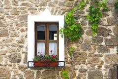 Vecchia finestra di legno con i fiori sulla parete di pietra Immagine Stock