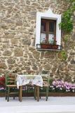 Vecchia finestra di legno con i fiori sulla parete di pietra Fotografia Stock