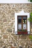 Vecchia finestra di legno con i fiori sulla parete di pietra Immagini Stock Libere da Diritti