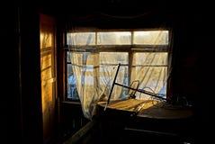 Vecchia finestra leggera con una tenda in una stanza scura Immagini Stock Libere da Diritti