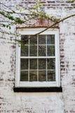 Vecchia finestra sulla casa con mattoni a vista imbiancata Fotografia Stock Libera da Diritti