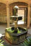 Vecchia fontana di pietra all'entrata della chiesa a Barcellona, Spagna Immagine Stock