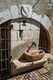 Vecchia fontana di pietra con i portoni del ferro e lo schermo araldico sull'arco a Annecy Immagine Stock Libera da Diritti