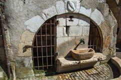 Vecchia fontana di pietra con i portoni del ferro e lo schermo araldico sull'arco a Annecy Immagini Stock