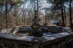 Vecchia fontana rovinata abbandonata in parco invaso Immagini Stock