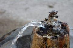 Vecchia fontanella del bronzo dell'annata su un seminterrato di pietra Fotografia Stock