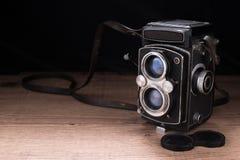 Vecchia foto della macchina fotografica su una superficie di legno Fotografie Stock