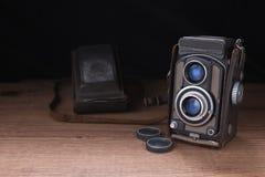 Vecchia foto della macchina fotografica su una superficie di legno Immagine Stock