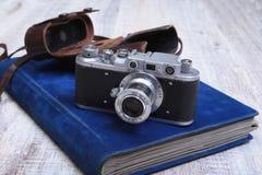 Vecchia foto-macchina fotografica d'annata del film nel caso ed in album di cuoio Fotografie Stock