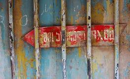 Vecchia freccia che indica ad un'entrata della costruzione Immagine Stock Libera da Diritti