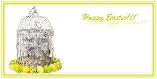 Vecchia gabbia del metallo con le uova di Pasqua su fondo isolato bianco immagini stock