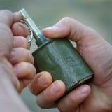 Vecchia granata antiuomo nelle mani di un uomo fotografia stock