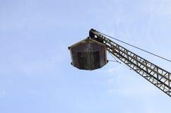 Vecchia gru a benna meccanica gialla della copertura superiore sul fondo del cielo blu immagini stock libere da diritti