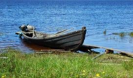 Vecchia imbarcazione a motore di legno di pesca dalla banca del lago Immagini Stock