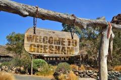 vecchia insegna di legno con il benvenuto del testo a Gresham appendendo su un ramo immagine stock libera da diritti