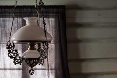 Vecchia lampada di vetro antica che pende dal soffitto in salone rustico fotografia stock