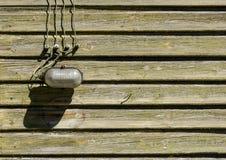 Vecchia lampada di vetro con i cavi sulla parete di legno Immagini Stock Libere da Diritti