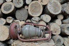 Vecchia lampada a olio sui precedenti di legna da ardere fotografia stock