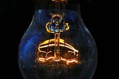 Vecchia lampadina che emette luce nello scuro Immagini Stock