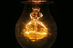 Vecchia lampadina che emette luce nello scuro Immagine Stock