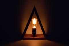 Vecchia lampadina d'ardore classica di Edison con il filamento in lampada del sottotetto che partecipa nel triangl di legno come  Fotografia Stock
