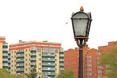 Vecchia lanterna della via del ferro contro il contesto delle case Immagini Stock