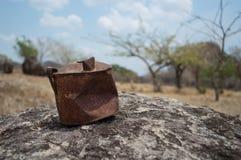Vecchia latta arrugginita su una roccia in un deserto fotografie stock