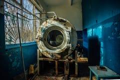 Vecchia lavatrice industriale tagliata arrugginita con la pittura della sbucciatura nella stanza di lavanderia all'ospedale psich Fotografie Stock Libere da Diritti