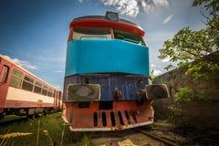 Vecchia locomotiva nel cimitero del treno con erba verde ed alberi nei precedenti e nel grande cielo nuvoloso immagine stock libera da diritti