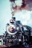 Vecchia locomotiva a vapore contro il cielo nuvoloso blu, treno d'annata Fotografie Stock Libere da Diritti
