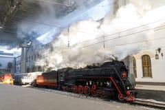 Vecchia locomotiva a vapore nera in Russia nell'inverno sui precedenti della stazione ferroviaria di Mosca Immagine Stock